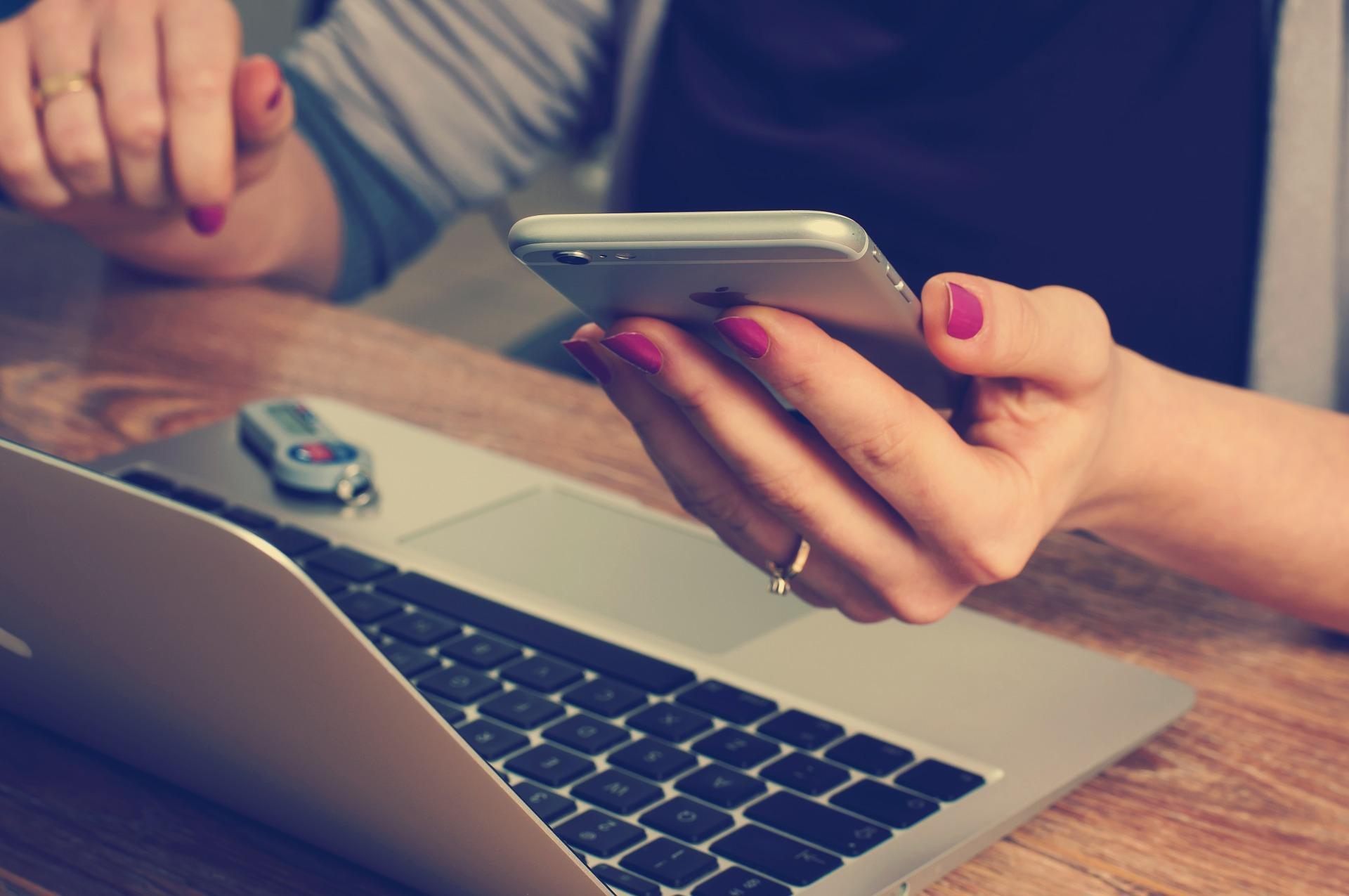 Frau arbeitet mit Smartphone und Laptop