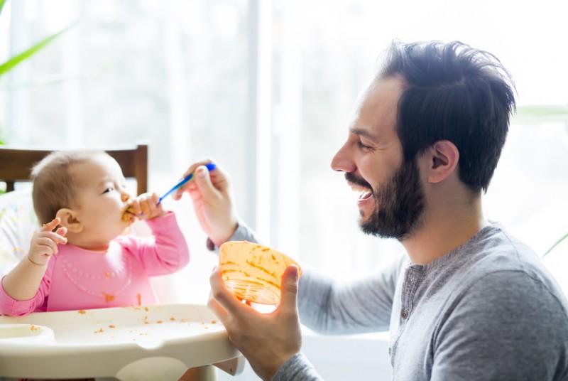 Vater beim Füttern seiner kleinen Tochter