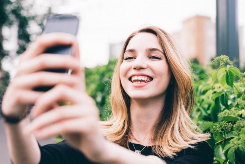 Junge Frau, die ein Selfie schießt