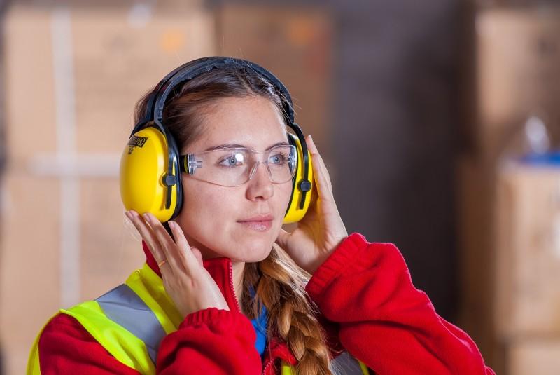 Frau in Arbeitsmontur mit Kopfhörern